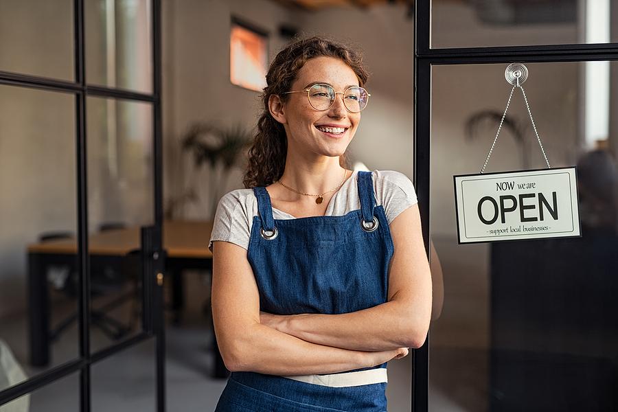 Portrait of happy waitress standing at restaurant entrance. Port