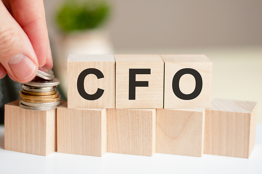 The Word Cfo Written On Wood Cubes. A Man's Hand Places The Coin